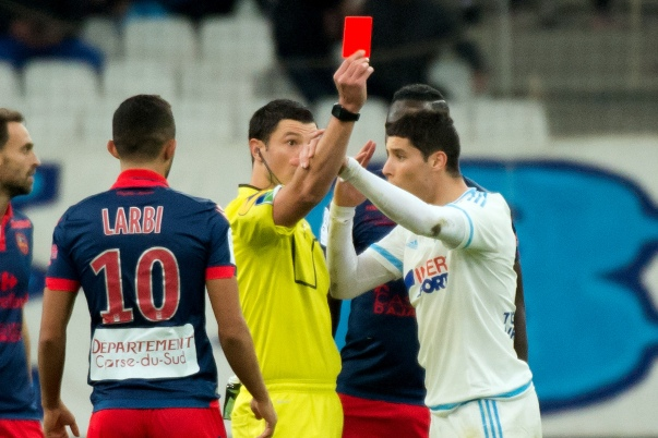 Marseille's Moroccan midfielder Abdelaziz Barrada (R) is given a red card by referee Nicolas Rainville (C) wduring the French L1 football match Olympique de Marseille versus Gazelec-Ajaccio on December 13, 2015 at the Velodrome stadium in Marseille, southern France. AFP PHOTO / BERTRAND LANGLOIS / AFP / BERTRAND LANGLOIS